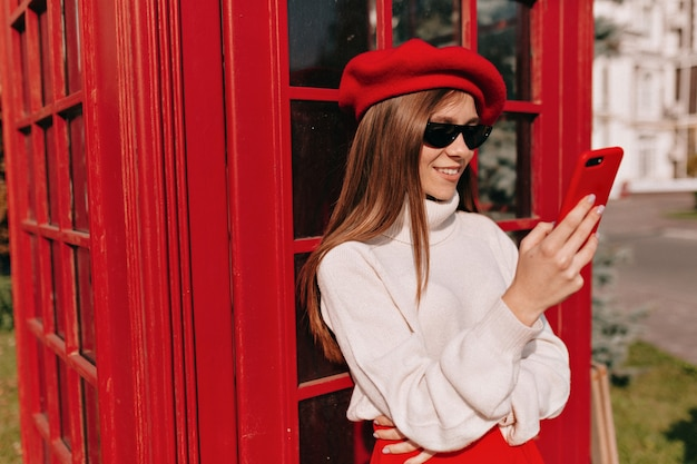 Jolie dame charmante habillée en tenue française debout avec smartphone