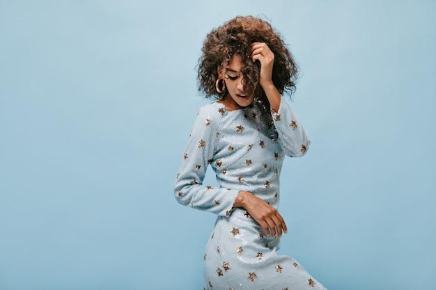 Jolie dame avec une coiffure brune frisée en robe brillante à la mode et des boucles d'oreilles modernes rondes posant sur un mur bleu.