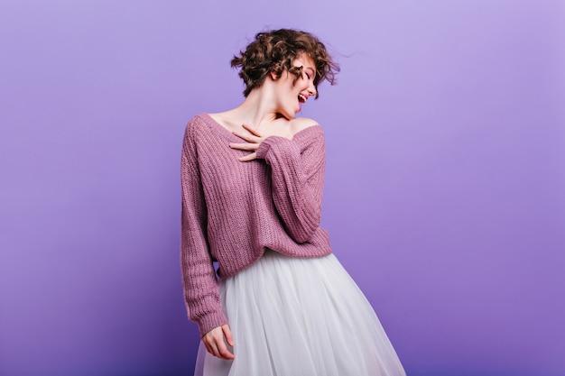 Jolie dame en collants noirs faisant des grimaces pendant la séance photo en intérieur. fille à la mode en chapeau et jupe blanche s'amuser sur le mur violet.