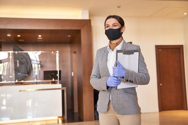 Jolie dame en costume et masque médical tenant un presse-papiers et regardant au loin