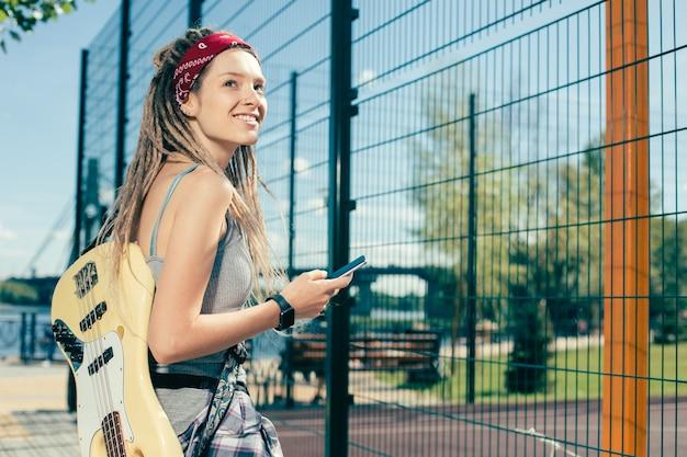 Jolie dame avec des dreadlocks souriant tout en marchant près du terrain de sport avec sa guitare