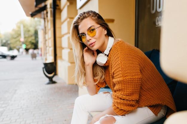 Jolie dame en jean blanc et cardigan marron à la recherche avec un sourire intéressé tout en se reposant sur un banc