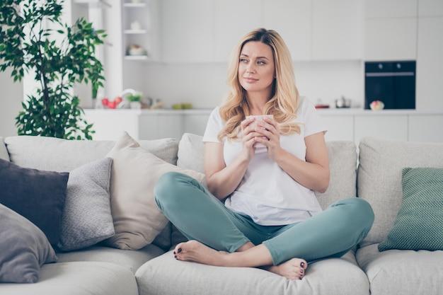 Jolie dame joyeuse domestique se détendre s'asseoir confortable canapé tenir mug dream