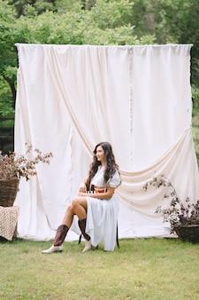 Jolie dame en longue robe blanche avec ceinture assis et souriant dans le jardin avec mur blanc pendant la journée.