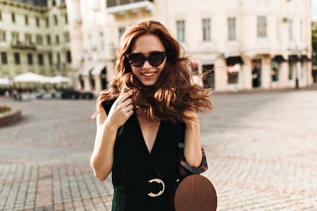 Jolie dame à lunettes de soleil pose à l'extérieur