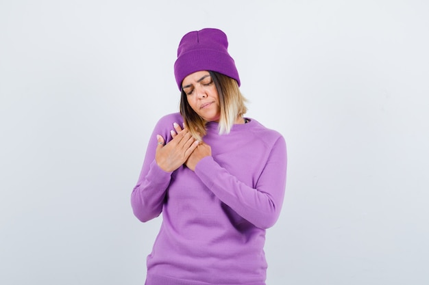 Jolie dame avec les mains sur la poitrine en pull, bonnet et l'air contrarié, vue de face.