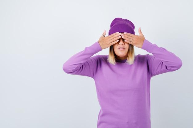 Jolie dame avec les mains sur les yeux en pull, bonnet et semblant excitée. vue de face.