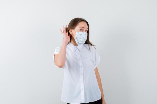 Jolie dame avec masque entendant la conversation