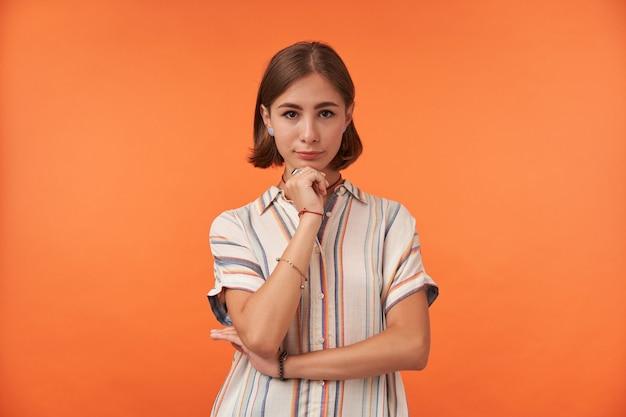 Jolie dame sur un mur orange, pliant les mains et touchant son menton, portant une chemise rayée et des bracelets.