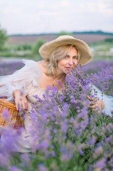 Jolie dame mûre dans un chapeau et une robe élégants, accroupie et appréciant le parfum de la lavande en fleurs