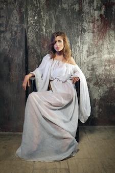 Jolie dame mystique en robe blanche gothique dans un cachot souterrain