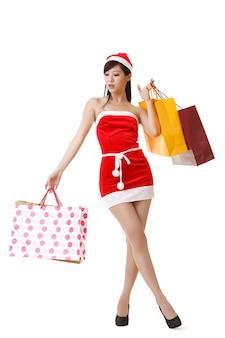 Jolie dame de noël tenant des sacs à provisions, portrait en pied isolé sur fond blanc.
