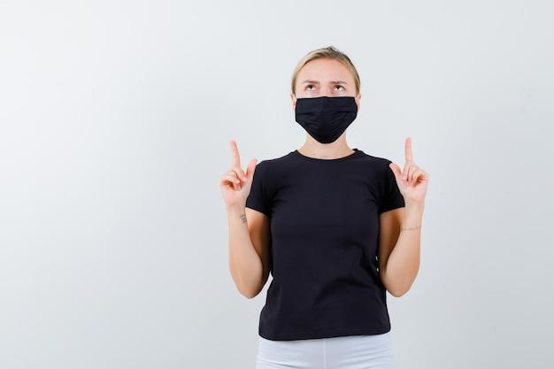 Jolie dame pointant vers le haut en t-shirt noir, masque noir et semblant reconnaissante isolée