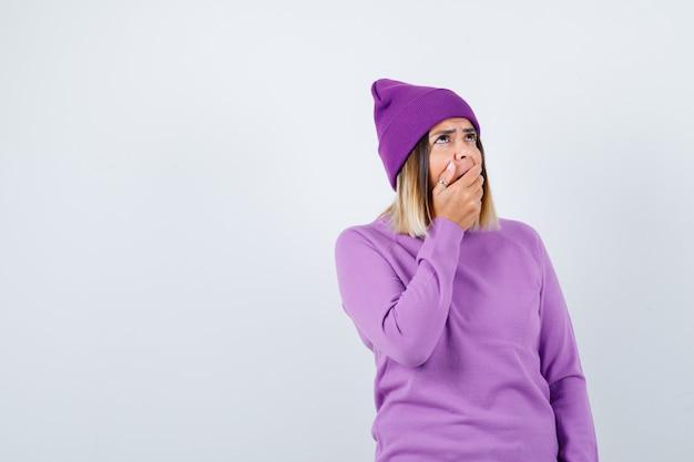 Jolie dame en pull, bonnet avec la main sur la bouche ouverte, levant les yeux et l'air surpris, vue de face.