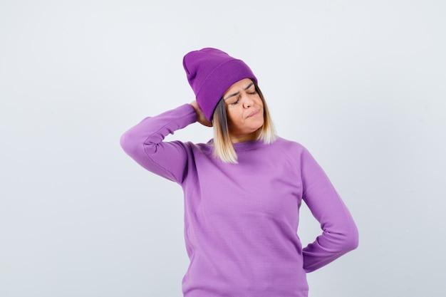 Jolie dame en pull, bonnet avec la main derrière la tête, fermant les yeux et l'air triste, vue de face.