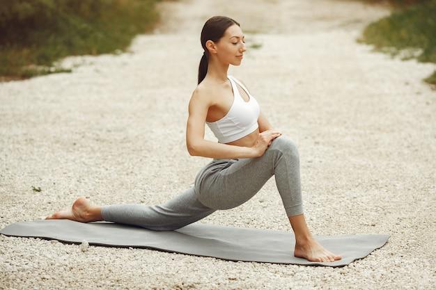 Jolie dame s'entraînant sur une plage d'été. brunette faisant du yoga. fille en tenue de sport.