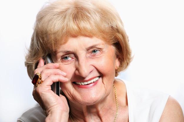 Une jolie dame senior parlant au téléphone sur fond blanc