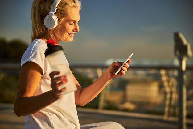 Jolie dame souriante tenant une bouteille d'eau et un smartphone tout en écoutant de la musique avec des écouteurs sans fil dans la rue