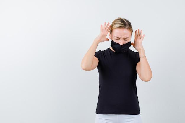 Jolie dame en t-shirt noir, masque noir gardant les mains levées isolées