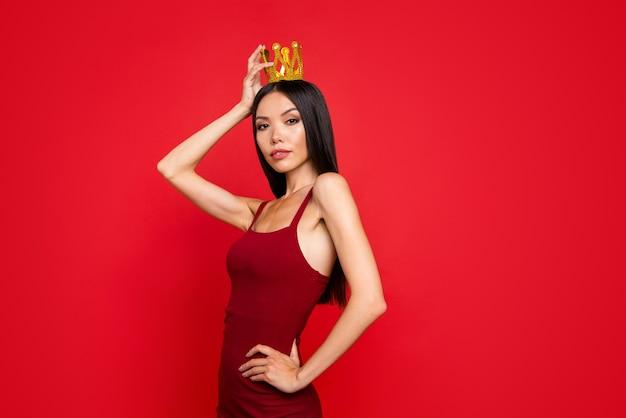 Jolie dame tenir la main sur la couronne de taille isolée sur le mur rouge