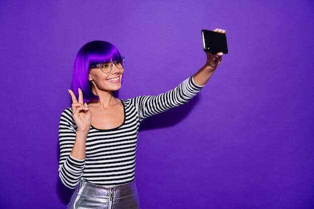 Jolie dame tenir la main téléphone prenant selfies montrant le symbole v-signe porter des spécifications pull rayé fond violet isolé