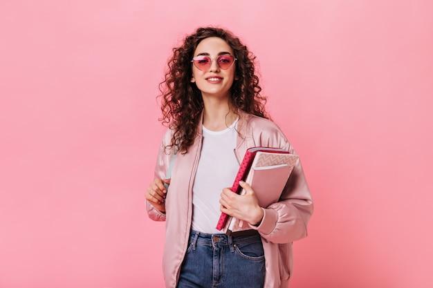 Jolie dame en tenue rose et lunettes de soleil tenant un livre