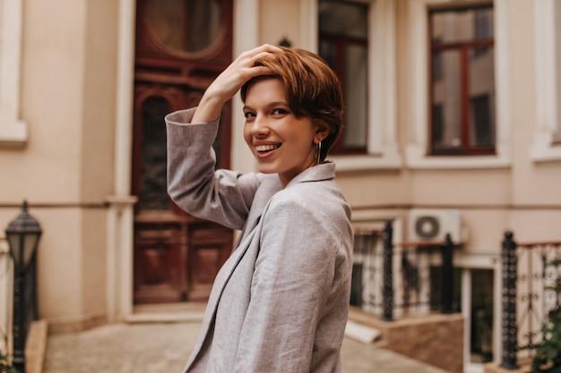 Jolie dame en veste souriant et touchant ses cheveux contre un beau bâtiment. femme gaie en costume gris en riant et posant à l'extérieur