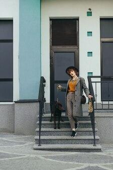Jolie dame en vêtements élégants et chapeau pose à la caméra avec un chiot en laisse