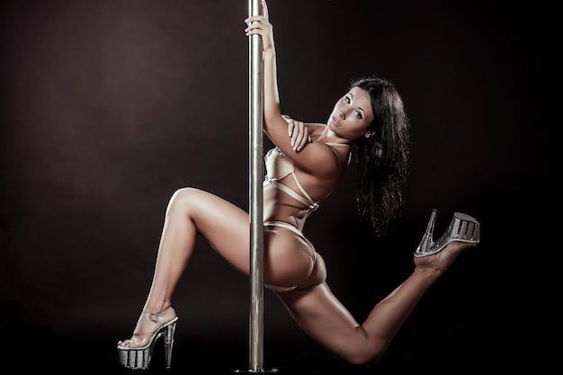 Jolie danseuse de pole femme sexy effectuant sur fond gris