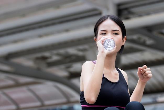 La jolie demoiselle boit de l'eau après les exercices du matin.