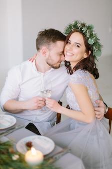 Jolie demoiselle d'honneur en couronne de pin et groomman à la table de mariage étreindre et embrasser