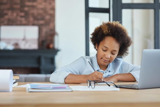 Jolie écolière adolescente métisse à la recherche de concentration à l'aide d'un ordinateur portable tout en prenant des notes en ligne