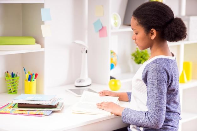 Jolie écolière assise à la table et lisant un livre.