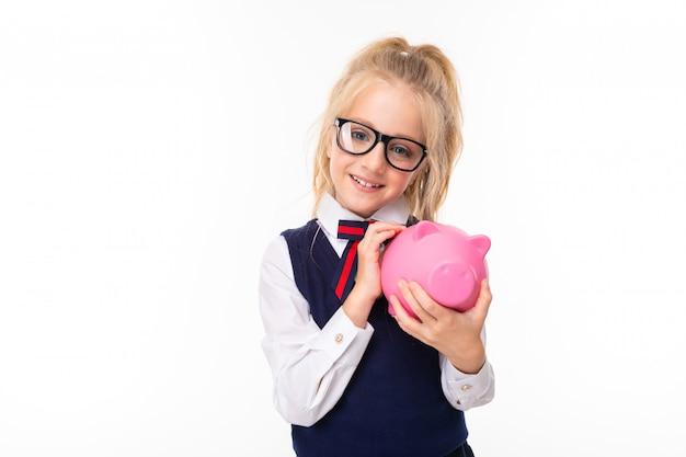 Jolie écolière aux cheveux blonds en costume d'école sourit et détient une tirelire cochon rose avec de l'argent isolé sur fond blanc