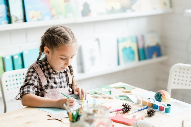 Jolie écolière décontractée avec un pinceau dessinant une photo de noël par bureau tout en travaillant individuellement