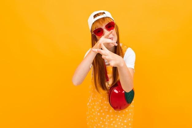 Jolie écolière grimace sur une orange, avec une grimace sur son visage