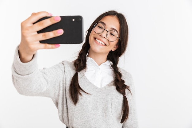 Jolie écolière heureuse portant unifrom debout isolée sur un mur blanc, prenant un selfie