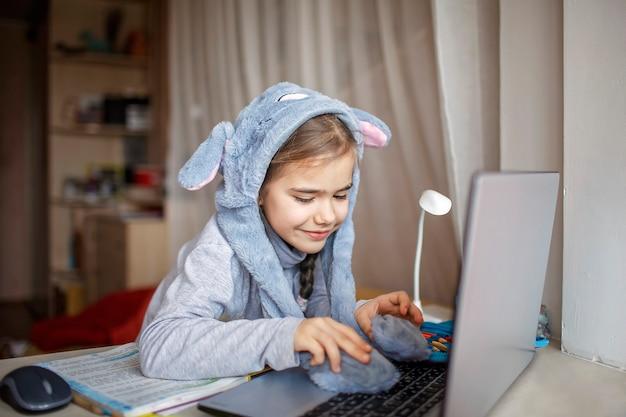 Jolie écolière portant un chapeau de lapin drôle avec des oreilles pendant la leçon en ligne ennuyeuse