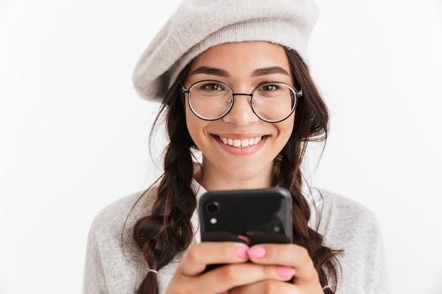 Jolie écolière souriante vêtue d'unifrom debout isolée sur un mur blanc, tenant un téléphone portable