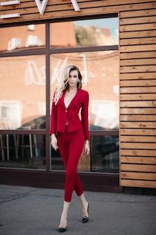 Jolie élégance élégante dame en costume rouge et chaussures noires