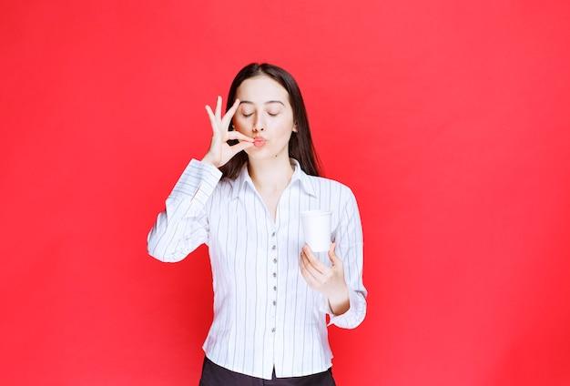 Jolie employée de bureau posant avec une tasse de thé en plastique sur un mur rouge.