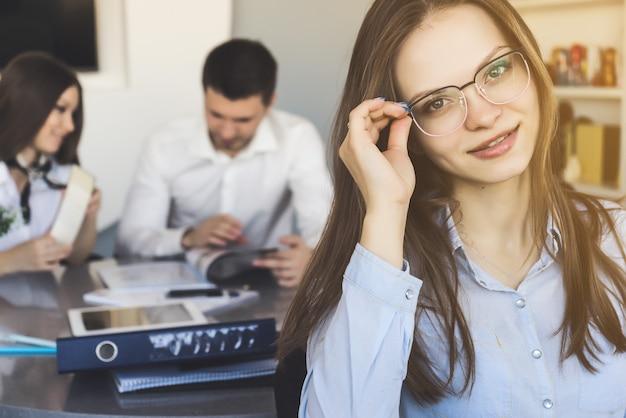 Une jolie employée de bureau tient des lunettes sur fond avec l'équipe de travail.