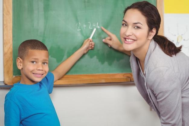 Jolie enseignante aidant l'élève au tableau