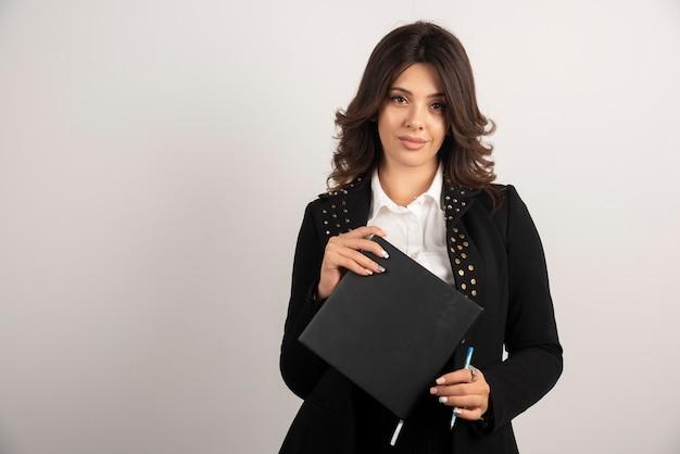 Jolie enseignante posant avec un livre sur blanc.