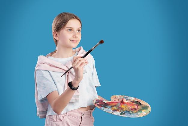 Jolie étudiante adolescente en t-shirt et jeans tenant un pinceau et une palette de couleurs tout en allant peindre à la leçon à l'école des arts