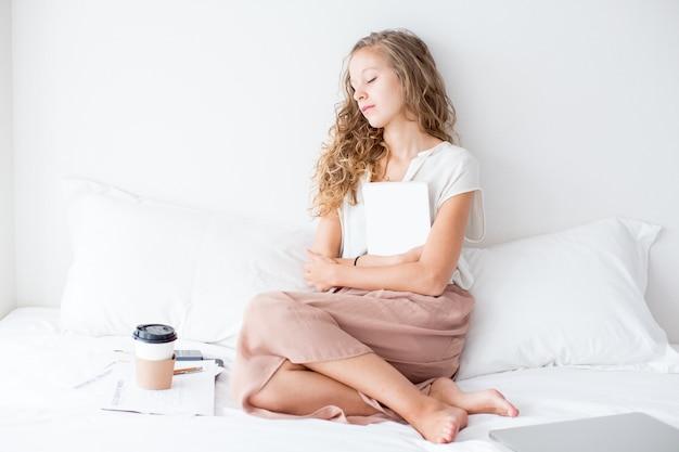 Jolie étudiante debout sur un lit avec un livre