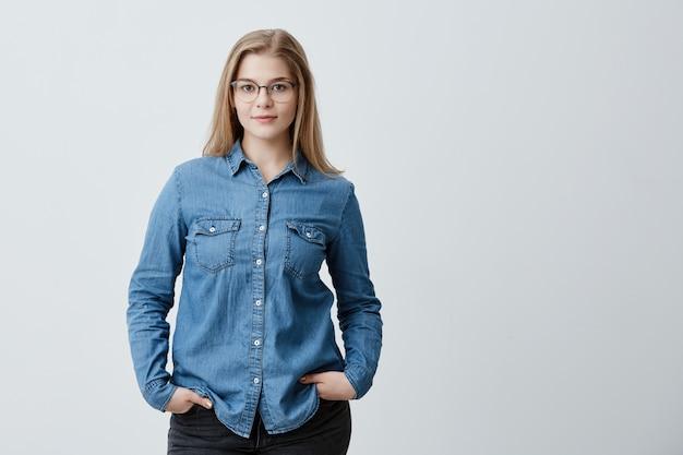 Jolie étudiante élégante avec des cheveux blonds raides et des lunettes vêtues d'une chemise en jean posant à l'intérieur, tenant ses mains dans les poches. concept de personnes, de beauté et de style de vie