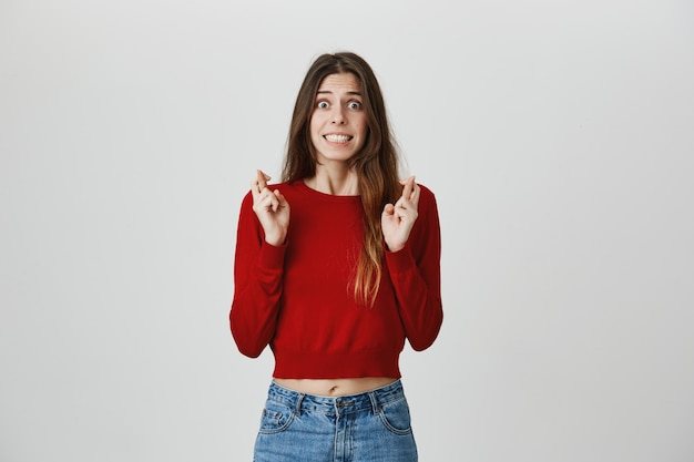Une jolie étudiante excitée et pleine d'espoir croise les doigts pour faire un vœu, plaider