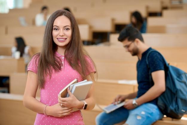 Jolie étudiante gardant des livres dans la classe.