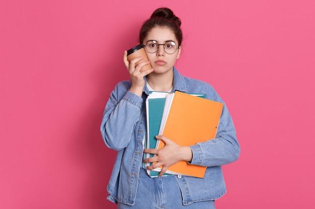 Jolie étudiante jeune femme touchant sa joue avec du café à emporter, tenant un dossier en papier,